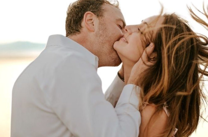 Man kissing a woman on the neck